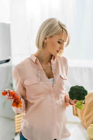 Photo for Attractive blonde and pregnant woman looking at organic broccoli - Royalty Free Image