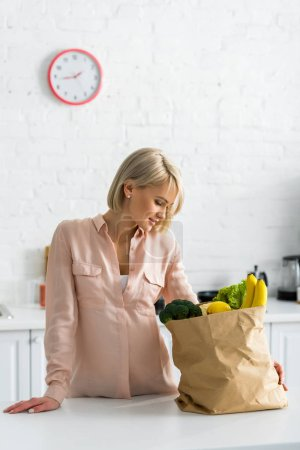 Photo for Attractive blonde, pregnant woman looking at paper bag in kitchen - Royalty Free Image