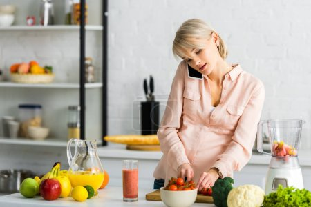 Photo pour Blonde pregnant woman talking on smartphone in kitchen near fruits and vegetables - image libre de droit