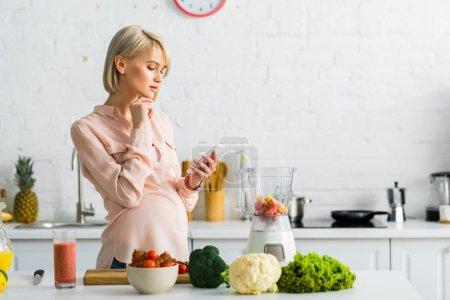 Photo pour Femme enceinte blonde utilisant le smartphone dans la cuisine près de tomates cerises sur planche à découper - image libre de droit