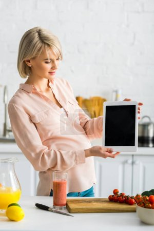 young pregnant woman holding digital tablet with blank screen