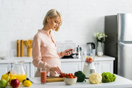 Photo for Pregnant blonde woman holding smartphone in kitchen with fruits and vegetables - Royalty Free Image