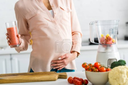 Photo for Cropped view of pregnant woman holding glass of smoothie near vegetables in kitchen - Royalty Free Image