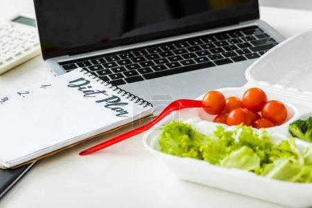 Foto de Verduras sabrosas cerca de Notebook con letras de plan de dieta y computadora portátil - Imagen libre de derechos