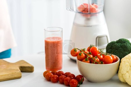 Photo for Glass of tasty smoothie near cherry tomatoes and blender - Royalty Free Image