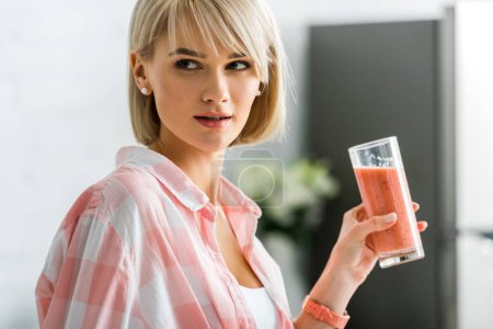 Photo for Attractive blonde woman holding glass of smoothie in kitchen - Royalty Free Image