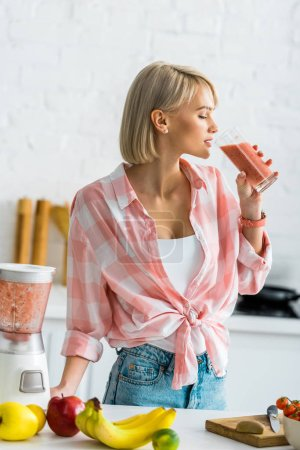 Photo for Attractive blonde woman drinking tasty smoothie in kitchen - Royalty Free Image