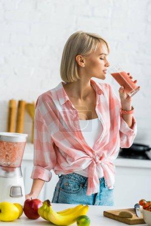Photo pour Femme blonde attirante buvant le smoothie savoureux dans la cuisine - image libre de droit