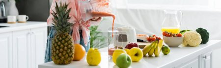 Photo for Panoramic shot of young woman pouring tasty smoothie in glass - Royalty Free Image