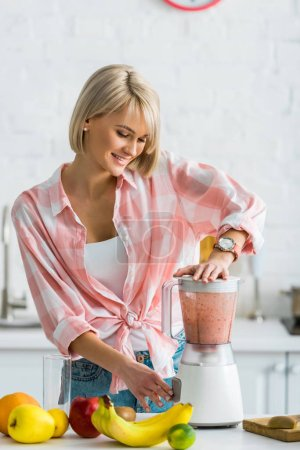 Photo for Happy young woman preparing delicious smoothie in blender - Royalty Free Image