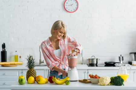 Photo for Happy young woman preparing tasty nutritious smoothie in blender - Royalty Free Image