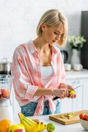 Photo pour Jeune femme pelant kiwi fruits près des ingrédients dans la cuisine - image libre de droit