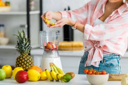 Photo for Cropped view of young woman adding ingredients in blender  near fruits - Royalty Free Image