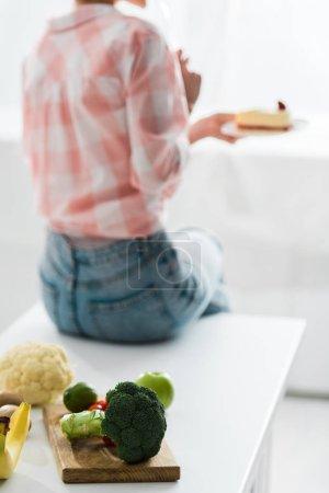 Foto de Frutas y verduras orgánicas cerca de la mujer que sostiene la torta dulce - Imagen libre de derechos