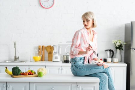 Photo for Blonde girl holding fork and saucer with sweet cake and looking at organic fruits and vegetables - Royalty Free Image