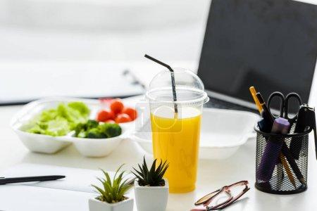 Photo pour Jus d'orange et plantes vertes près de savoureux légumes et ordinateur portable avec écran blanc - image libre de droit