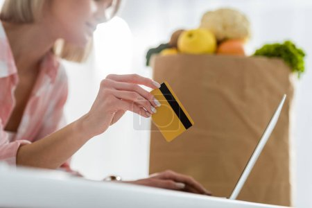Foto de Cropped view of girl holding credit card while using laptop near paper bag with groceries - Imagen libre de derechos