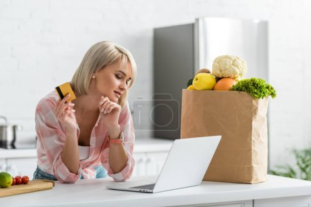 Foto de Attractive blonde girl holding credit card while looking at laptop near paper bag with groceries - Imagen libre de derechos