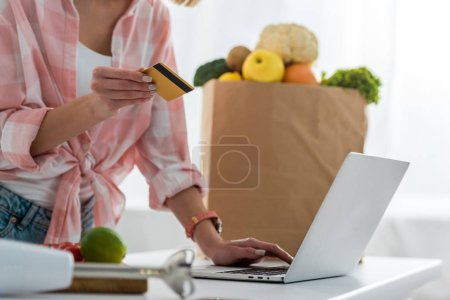 Foto de Cropped view of young woman holding credit card while using laptop near paper bag with groceries - Imagen libre de derechos