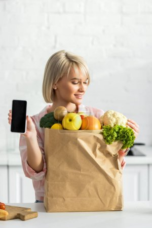 Photo for Cheerful blonde woman holding smartphone with blank screen near paper bag with ingredients - Royalty Free Image