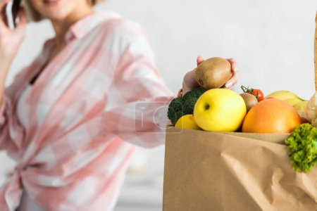 Photo for Cropped view of woman holding kiwi fruit near paper bag with food - Royalty Free Image