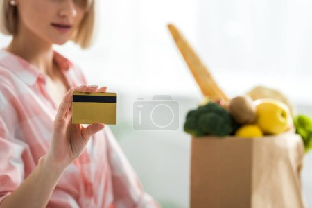 Photo for Cropped view of woman holding credit card near groceries - Royalty Free Image