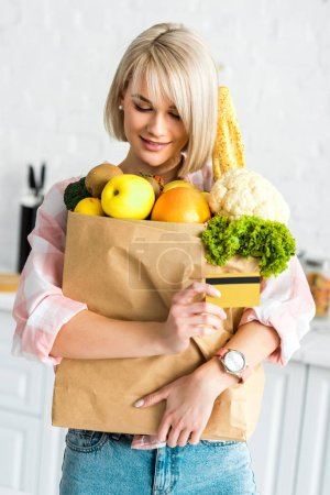 Photo for Happy blonde girl holding credit card while hugging paper bag with groceries - Royalty Free Image