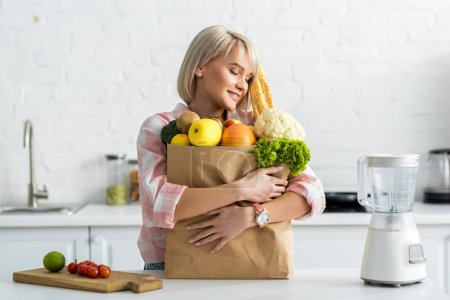 Photo for Happy blonde young woman embracing paper bag with groceries - Royalty Free Image