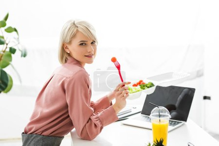Photo for Cheerful blonde freelancer near laptop with blank screen and vegetables in takeaway box - Royalty Free Image