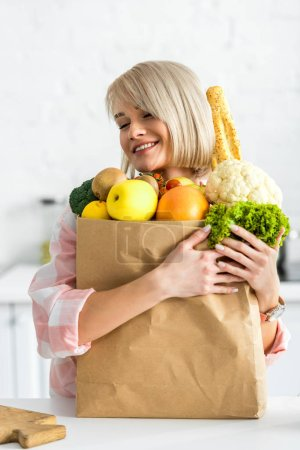 Photo for Happy blonde young woman hugging paper bag with groceries - Royalty Free Image