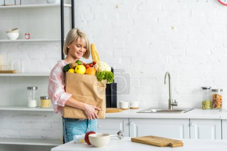 Photo for Cheerful blonde young woman holding paper bag with groceries - Royalty Free Image