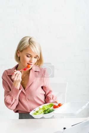 Photo for Blonde girl eating cherry tomato and looking at takeaway box - Royalty Free Image