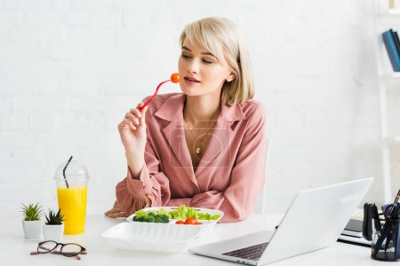 Photo for Blonde freelancer holding fork with cherry tomato near laptop - Royalty Free Image