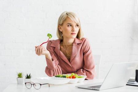Photo pour Attrayant freelance tenant fourchette avec brocoli près d'un ordinateur portable - image libre de droit