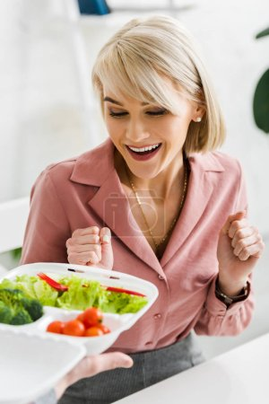 cropped view of man holding takeaway box with vegetables near excited blonde woman