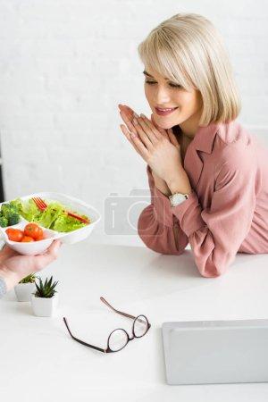 Photo pour Vue recadrée de l'homme tenant boîte à emporter avec des légumes près jeune femme heureuse - image libre de droit