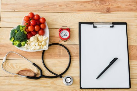 Photo for Top view of blank clipboard with pen near stethoscope, alarm clock and tasty vegetables on heart-shape plate - Royalty Free Image