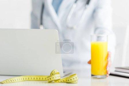 Photo pour Vue recadrée de nutritionniste retenant le verre de jus d'orange frais près de la bande de mesure - image libre de droit