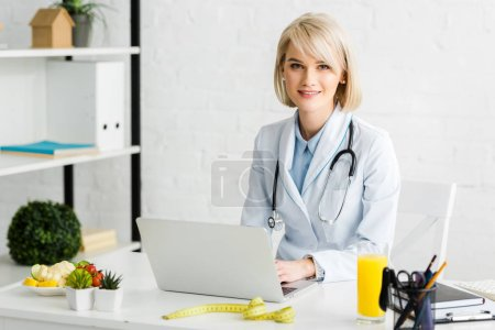 Photo for Cheerful blonde nutritionist sitting near laptop and glass of fresh orange juice - Royalty Free Image