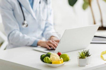 Photo pour Vue recadrée de nutritionniste à l'aide d'un ordinateur portable près de la plaque avec des aliments biologiques - image libre de droit