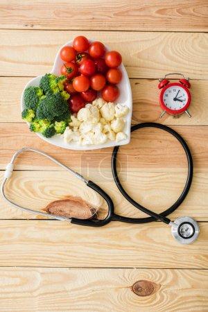 Photo pour Vue de dessus des légumes sur la plaque en forme de coeur près du stéthoscope et du réveil rétro sur la surface en bois - image libre de droit