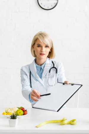 Photo for Attractive blonde nutritionist in white coat holding blank clipboard and pen - Royalty Free Image
