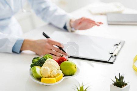 Photo pour Vue recadrée du nutritionniste tenant le stylo près du presse-papiers et de l'assiette avec des aliments biologiques - image libre de droit