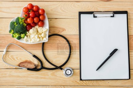 Photo for Top view of blank clipboard with pen near stethoscope and tasty vegetables on heart-shape plate - Royalty Free Image