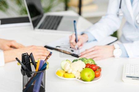 Photo pour Vue recadrée du diagnostic d'écriture de nutritionniste près du patient et de la plaque avec des aliments biologiques - image libre de droit