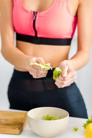 Photo for Cropped view of woman in sportswear holding salad leaves near bowl - Royalty Free Image