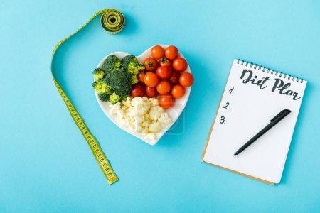 Photo pour Vue de dessus de légumes savoureux sur la plaque de coeur-forme près de la bande de mesure et cahier avec le lettrage de plan de régime sur le bleu - image libre de droit