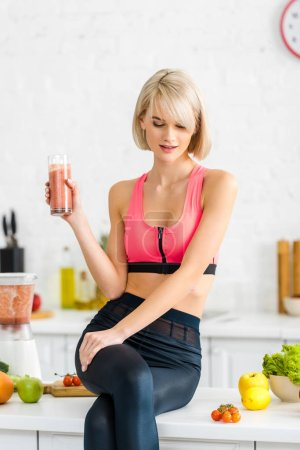 Photo for Attractive blonde woman in sportswear holding tasty smoothie in kitchen - Royalty Free Image