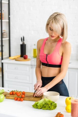 Photo for Attractive blonde woman in sportswear cutting cherry tomatoes near apples and vegetables - Royalty Free Image