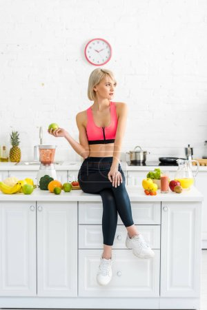 Photo for Attractive blonde woman in sportswear holding apple near ingredients in kitchen - Royalty Free Image